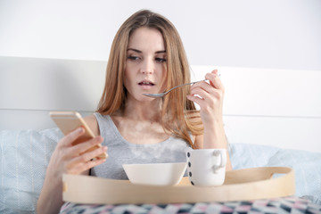 Morning at home, woman in bed eating breakfast