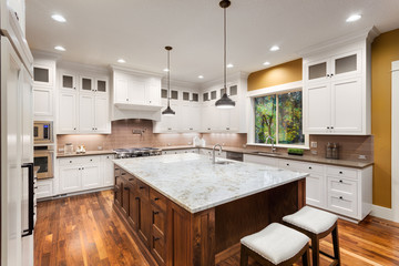 Kitchen Interior with Large Island, Sink, White Cabinets, Pendant Lights, and Hardwood Floors in New Luxury Home