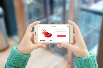 Online shopping with mobile phone. Modern user interface on horizontal device screen. Woman holding and show phone. Glass of business center in background.