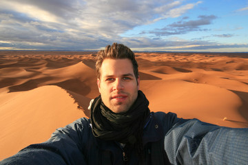 Male solo traveler taking selfie at dunes in Sahara desert, Morocco.