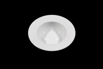 Small deep plate with wide shoulders on black background directly from high angle