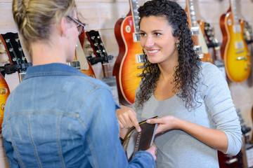 Sales clerk advising customer in musical instrument shop