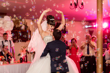 Wedding dance, happy couple dancing on wedding party with colorful special effects and bubble blower. Wedding day concept