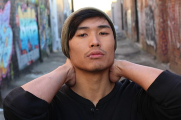 Asian man with piercing and beanie outdoors in the city
