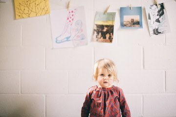 Portrait of young girl, pictures hanging on wall behind her
