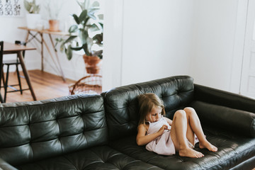 Young girl relaxing on sofa, using smartphone