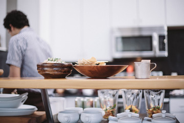 Bowls of food on serving shelf, person preparing food in kitchen behind