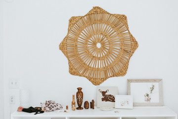 Wicker star on wall above variety of ornate objects on shelf