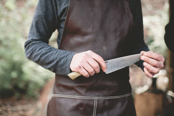 Person holding knife, feeling sharpness of blade