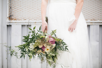 Bride holding bouquet of flowers, mid section