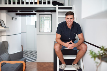 Smiling young man sitting in his modern loft apartment