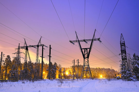 power transmission line poles in the winter evening