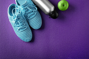 Clothes and items for sport on color background