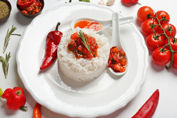 Cooked rice served with sauce and vegetables, closeup
