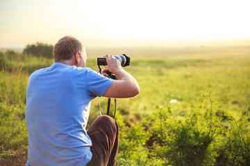 Professional photographer taking photo on savannah