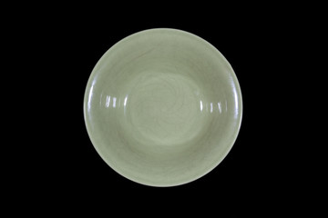 Soup deep green plate with round shoulders on wooden cutting board from above