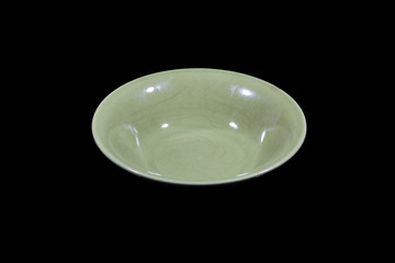Soup deep green plate with round shoulders on wooden cutting board from side