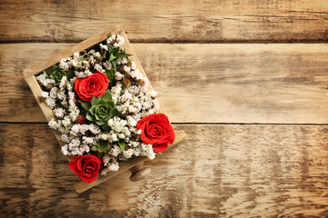 Box with beautiful flowers on wooden background