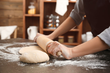 Young woman rolling out dough in kitchen