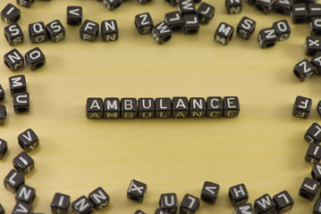 Word Ambulance on a wooden background