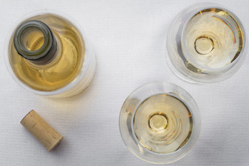 2 glasses of white wine on a white linen table top