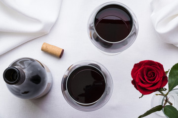 2 glasses of red wine with bottle, cork, and rose