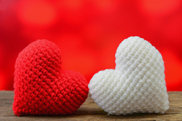 Red and white heart on wooden table and red background