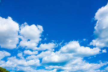 Blue sky background with clouds in bright sunny summer day.