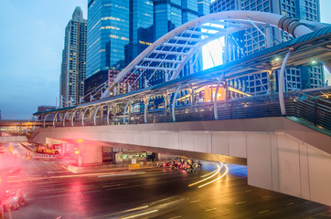 View of high buildings and public sky walk for transit between Sky Transit and Bus Rapid Transit Systems at Sathorn-Narathiwas junction at night