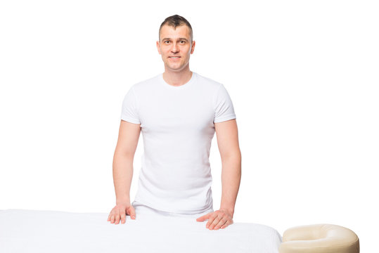 male masseur is waiting for a patient near a massage table in is