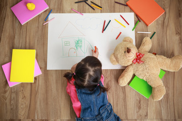 Little Asian girl drawing in paper on floor indoors, top view of