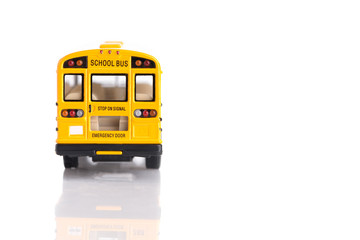Rear view of yellow school bus toy made from plastic and metal