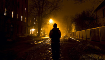 One man on the foggy street at night