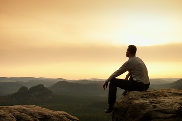 Adult hiker in black sit on mountain  edge. Man enjoying evening