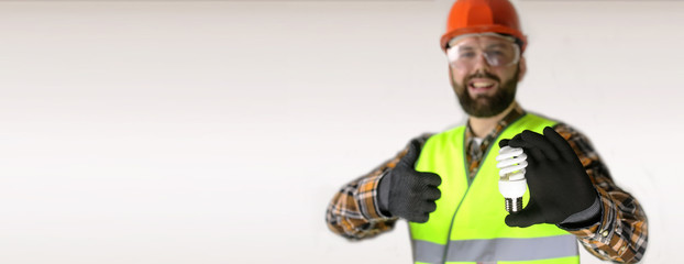 Worker in a helmet and protective clothing with a light bulb in