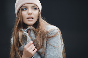 Young beautiful woman with model looks,beautiful makeup,long red hair,big black eye lashes,blue eyes,wearing a light gray coat and a pink sports hat posing on grey background in the city in the fall