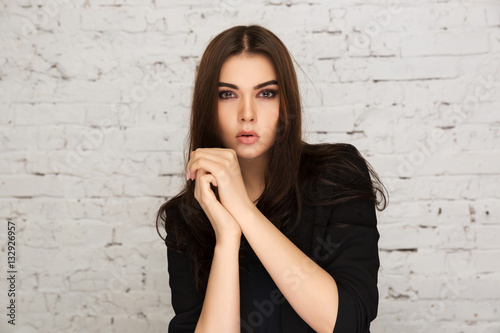 young fashion model in black jacket next to brick wall. Black Bedroom Furniture Sets. Home Design Ideas