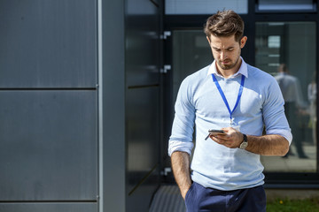 Businessman with smartphone text messaging outdoors