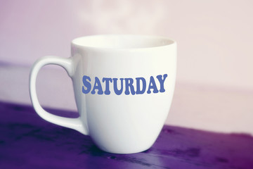 white cup with the word Saturday on it