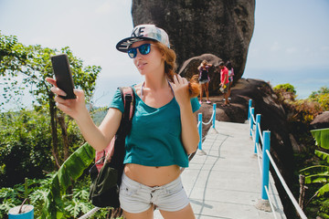 young stylish hipster ginger woman making selfie against mountai