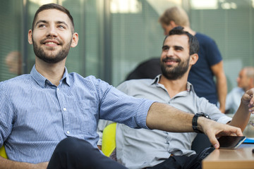 Businessmen listening to presentation in workshop