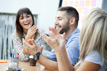Business people clapping hands in workshop