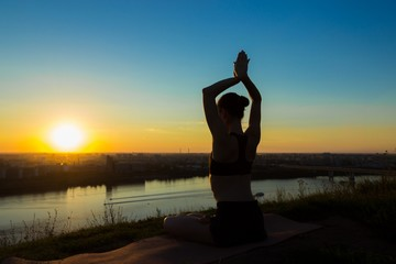 Sporty woman practicing yoga in the park at sunset - sun salutation. Sunset light, golden hour, lens flares. Freedom, health and yoga concept