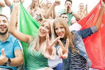 Group of soccer fans holding Italian flag