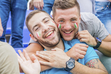 Two soccer fans with face paint in Italian colors