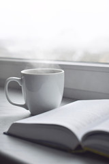 Cozy home still life: cup of hot coffee and opened book on windowsill against snow landscape outside. Winter holidays, Christmas time concept, free copy space