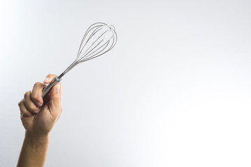 Hand holding stainless balloon whisk