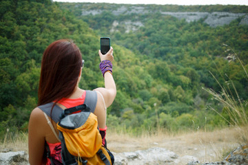 Woman photographs mountain using phone