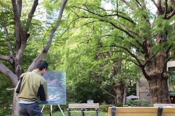 asian Japanese man artist painting stream picture in the Ueno park.