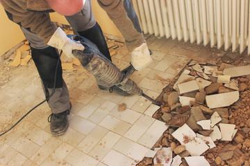 Mann entfernt mit elektrischem Meißel die Bodenfliesen in der Küche